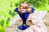 stock photo of chocolate fudge  - Chocolate Ice Cream with Fudge Sauce in a Blue Bowl on a Sunny Summer Day copy space for your text - JPG
