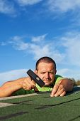 stock photo of shingles  - Man fastening bitumen roof shingles with nails and hammer  - JPG