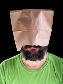 stock photo of ignorant  - Bearded man with paper bag on his head wearing a smile  - JPG
