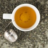 stock photo of black tea  - White cup of black tea on scattered tea over bamboo mat - JPG