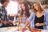 foto of three life  - Three Female Friends Making Pizza In Kitchen Together - JPG