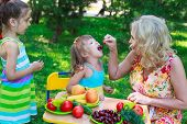 picture of child feeding  - Woman mother mum feeding her girl daughter kid child with cherry outdoors in garden - JPG