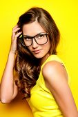 foto of spectacles  - Beauty portrait of a happy young woman in spectacles and bright yellow dress over yellow background - JPG