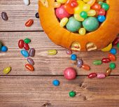 pic of foreshortening  - Jack o lantern halloween pumpkin filled with multiple colorful sweets and candies over the wooden board background composition - JPG