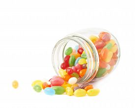 foto of jar jelly  - Colorful jelly bean candy sweets spilled out of a glass jar - JPG