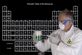 stock photo of chemical reaction  - Scientist holding a toxic chemical reaction in front of the periodic table of elements - JPG