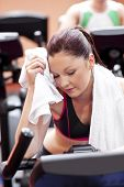 Exhausted Woman Wiping Her Face With A Towel Sitting On A Cross Trainer