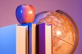 stock photo of midterm  - apple placed on a stack of books in front of an antique earth globe - JPG