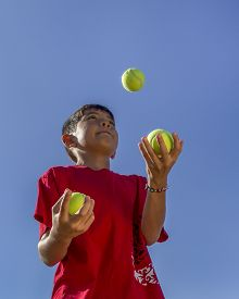 foto of juggling  - A young boy tries juggling against a bright blue sky - JPG
