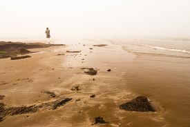 picture of girl walking away  - Woman walking away into fog at the sea shore - JPG