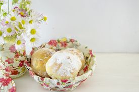 image of decoupage  - Homemade doughnuts sprinkled with powdered sugar in a decoupage decorated bowl with flowers on the table - JPG