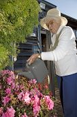 Elderly Woman Waters Her Plants