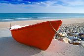 Small old red fishing boat on the beach