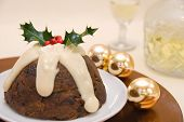 Christmas pudding with brandy sauce decorated with holly