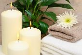 Calm and relaxing spa setting with lit candles and towels