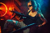 Young strong woman warrior with big guns in dramatic urban night scene poster