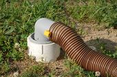 image of hookup  - RV sewer hose connected to sewer pipe at campsite - JPG