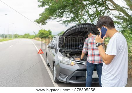 poster of Friends Fixing Car Broken Down On Highway  Calling For Help On Mobile Phone. Two Man Friends Talking