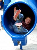 Blond boy child playing in a tube slide at the park