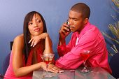 African American couple in a martini bar.Man talking on cell phone while the woman sits by annoyed a