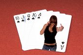 One of the highest hands in poker a Spades Royal Flush on a red felt gaming table