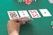 Texas Hold 'Um poker player peels back her cards to reveal a hearts Royal Flush