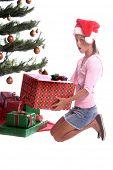 ein junges Mädchen reagiert mit Überraschung, wenn sie gefangen ist heimlich einen Blick auf die Geschenke unter dem christma