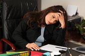 Female Executive stressed out and sitting at her desk  massaging her head to relieve a tension heada