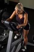 Beautiful blond woman during a cardio workout on an exercise bike in the gym