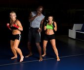Two beautiful young woman fighters working with their trainer in an MMA gym