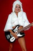 Blond snow bunny in a white furry coat and hat and black hot pants over a red background with an electric guitar poster