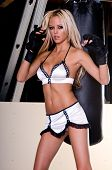 Sexy blond female MMA fighter training in the gym standing in front of a heavy bag