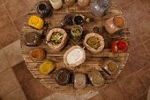 Variety Of Colorful Dried Herbs And Spices Displayed On Round Wooden Table In Plastic Free Store. To poster