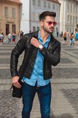 curious fashion man with red sunglasses going sightseeing the city and looking to side while holding poster
