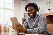 Happy casual african man using digital tablet at office. Portrait of smiling black businessman sitti poster
