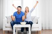people, family and leisure concept - happy smiling couple with popcorn watching tv at home poster