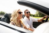 leisure, road trip, dating, couple and people concept - happy man and woman driving in cabriolet car poster