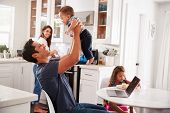 Young Hispanic family in their kitchen, dad lifting baby in the air, mum cooking at hob, close up poster