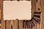 Row Of Yummy Chocolate Candies Near Blank Burnt Paper On Old Weathered Wooden Table poster