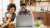 Remote Work And Freelance. Affectionate Black Woman Looking At Her Boyfriend Working On Laptop In Ki poster