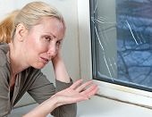 The housewife cries bad quality double-glazed window has burst because of cold weather