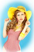 Bright Seductive Charming Pin-up Girl In A Pink Bathing Suit And A Broad Yellow Hat