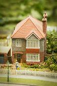 stock photo of milkman  - model of a generic british style suburban detached house and garden - JPG
