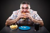 image of greedy  - Portrait of a greedy fat man eating burger on gray background - JPG