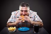 stock photo of greedy  - Portrait of a greedy fat man eating burger on gray background - JPG