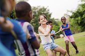 foto of tug-of-war  - Children and recreation group of happy multiethnic school kids playing tug - JPG