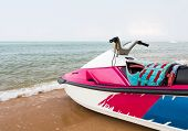stock photo of ski boat  - Pink jet ski close up parked on the beach - JPG