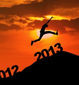 stock photo of leaping  - Man jump over 2013 number to embrace the new year - JPG