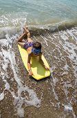 Child Surfing On The Beach