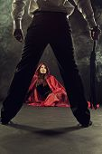 pic of submissive  - Red Riding Hood sits on the floor next to legs of Bad Wolf with lash - JPG